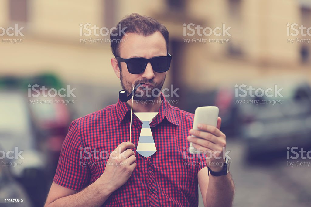 Happy man using cellphone and having fun outdoors. stock photo