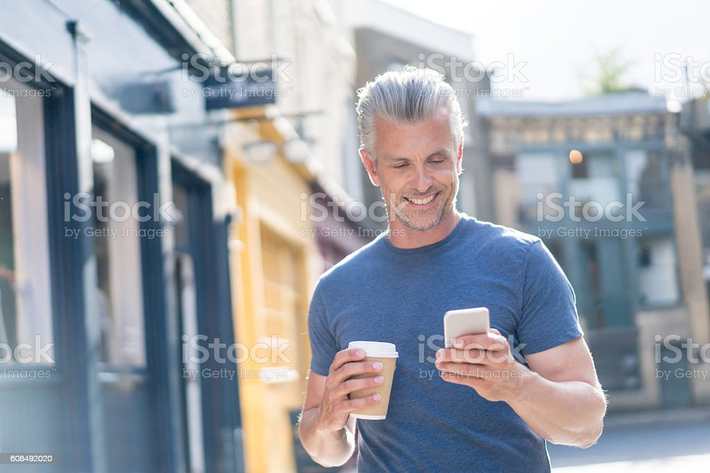Happy man using his cell phone outdoors stock photo