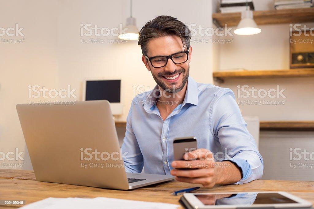 Happy man using smartphone stock photo
