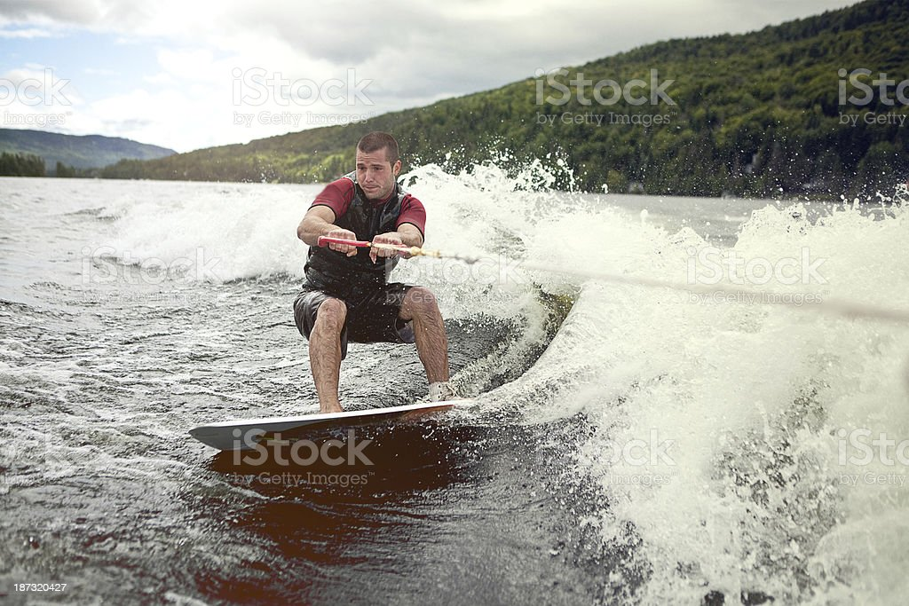Happy man wakeboarding in a lake stock photo