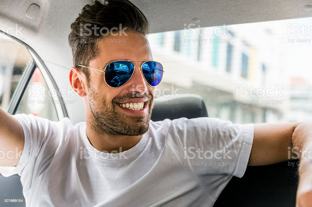 Happy man wearing sunglasses in car stock photo
