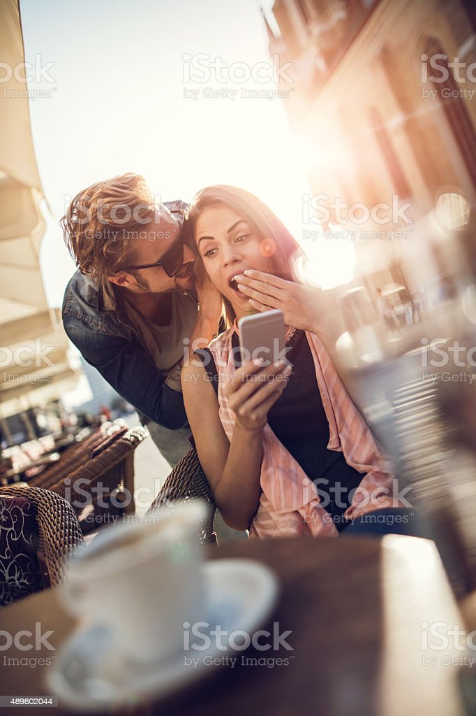 Happy man whispering shocking things to his girlfriend at cafe. stock photo