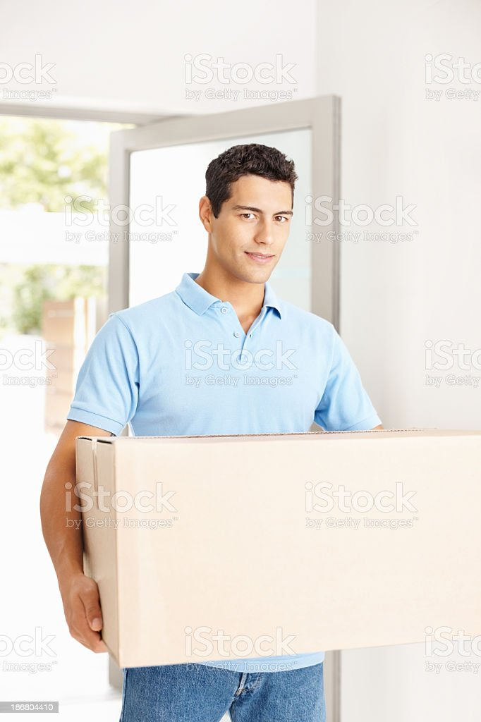 Happy man with box entering his new house royalty-free stock photo