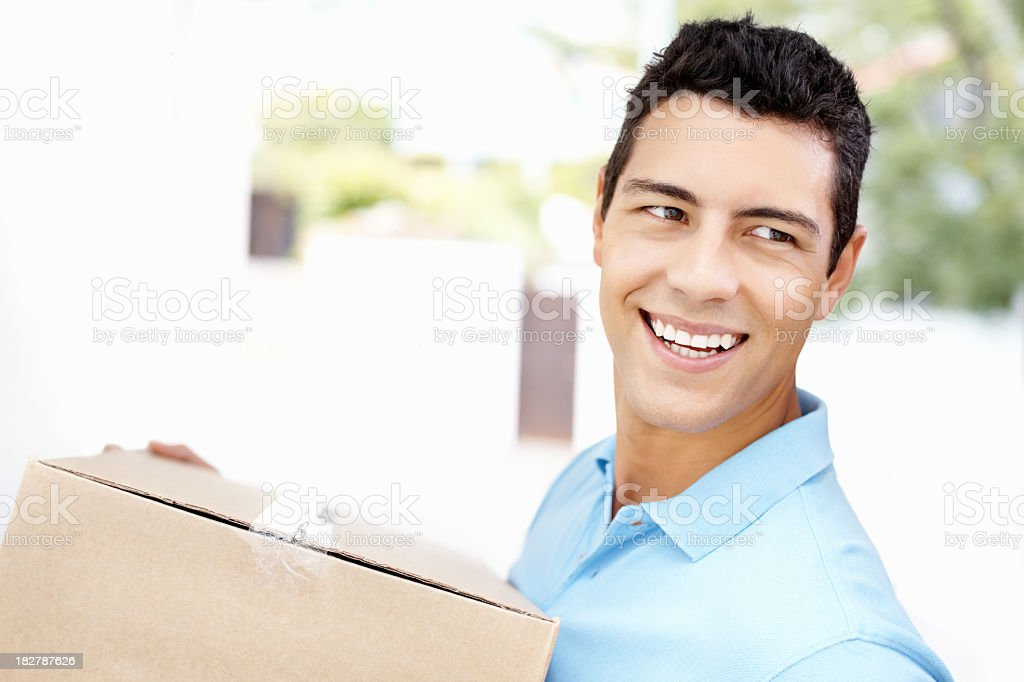 Happy man with box moving into new house smiling royalty-free stock photo