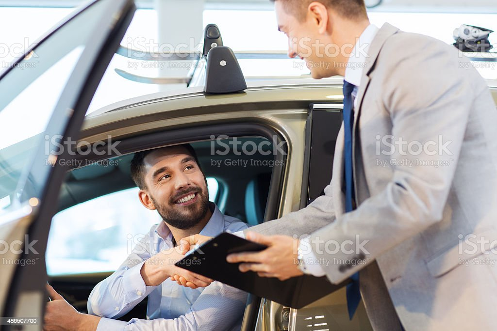 happy man with car dealer in auto show or salon stock photo