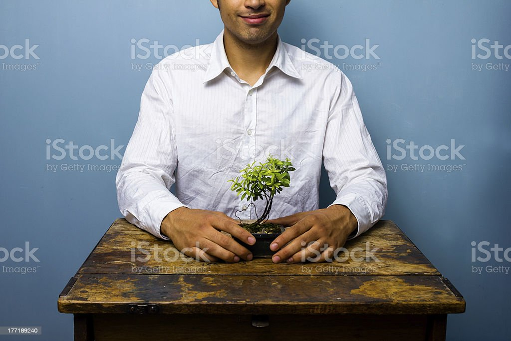 Happy man with his growing bonsai tree royalty-free stock photo