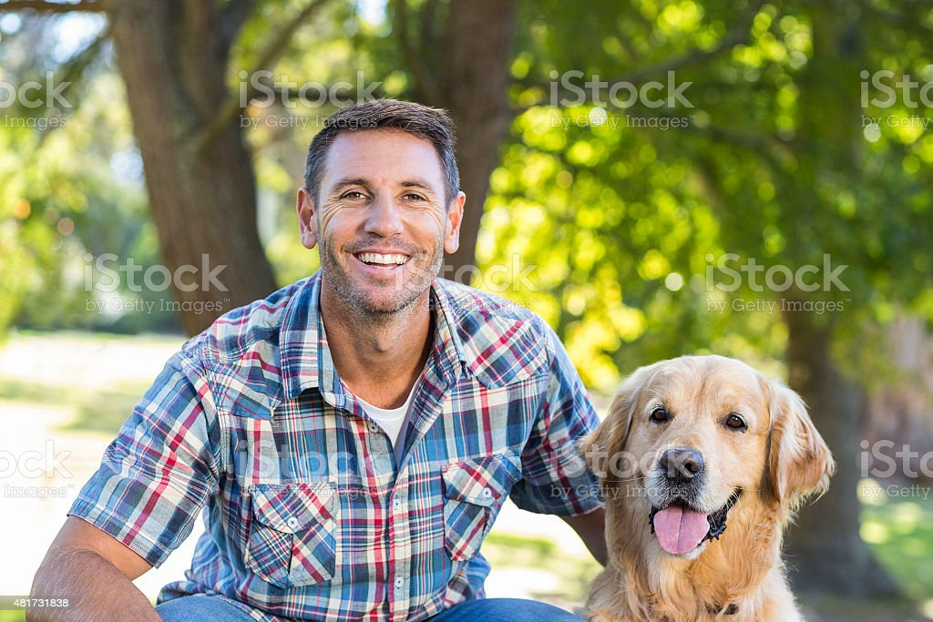 Happy man with his pet dog in park stock photo