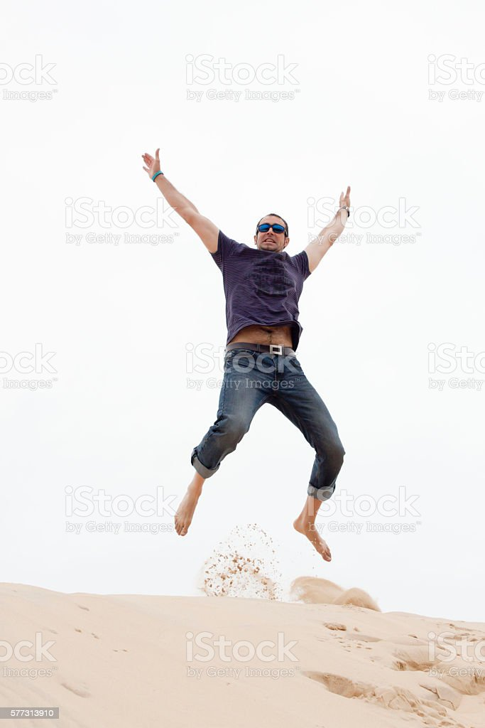 Happy man with sunglasses jumping in the sand stock photo
