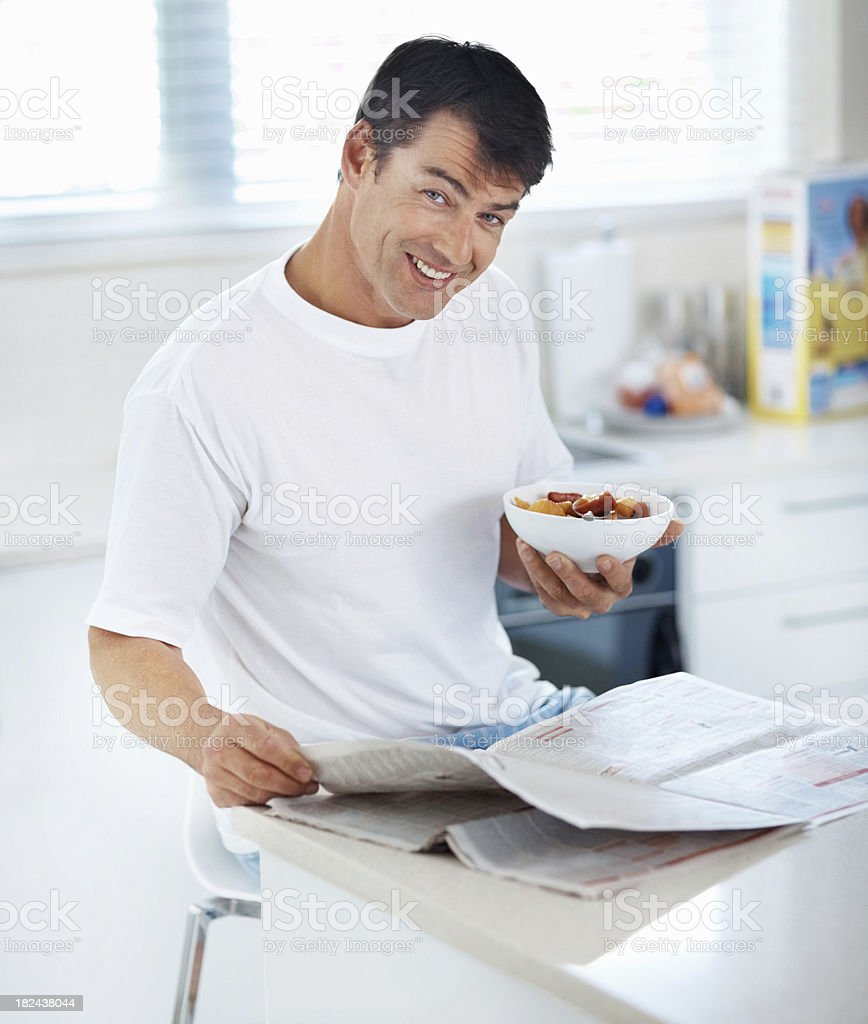 Happy man with the newspaper and a bowl of fruit royalty-free stock photo
