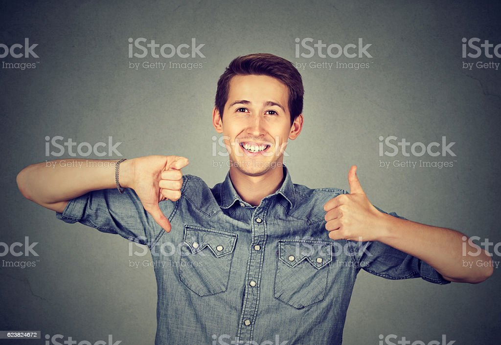 Happy man with thumbs down thumbs up gesture stock photo