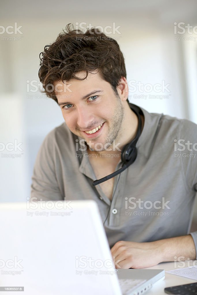 Happy man working with laptop and headset royalty-free stock photo