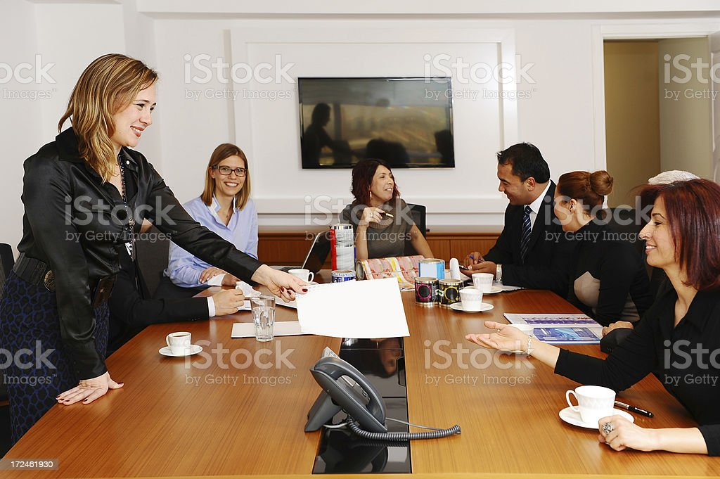 Happy manager giving folder to executive woman at meeting royalty-free stock photo