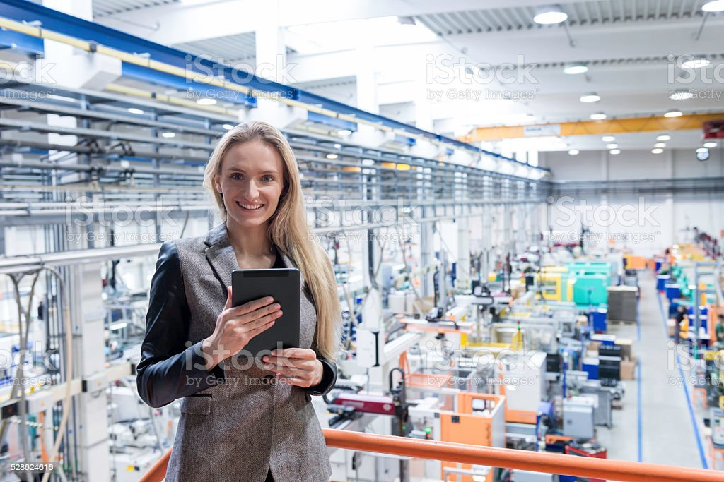 Happy manager with tablet on top of large factory stock photo