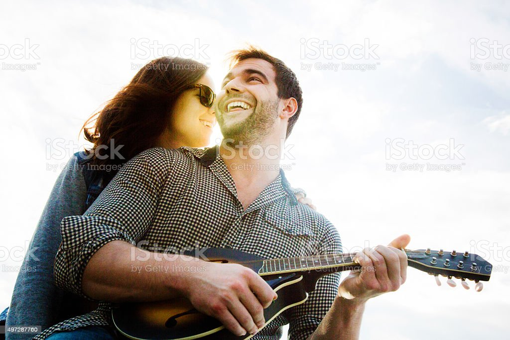 Happy mandolin player smiles as girlfriend whispers sweet things stock photo