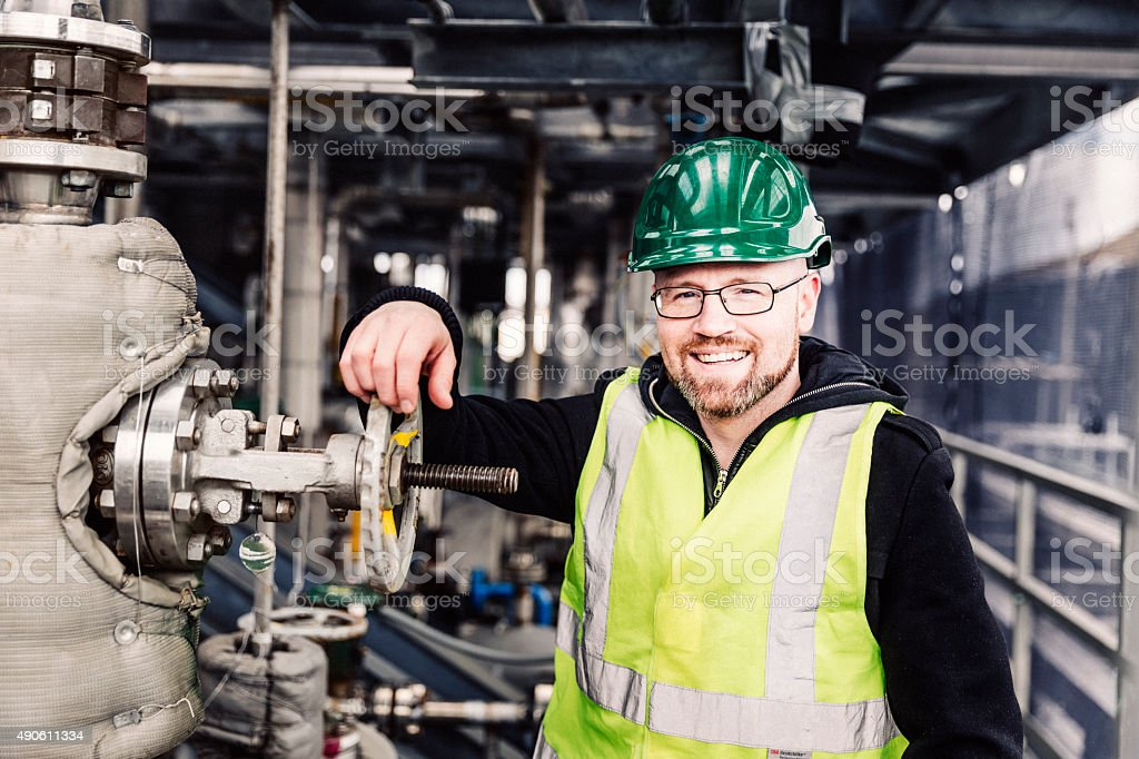 Happy manual worker standing by machine at factory stock photo