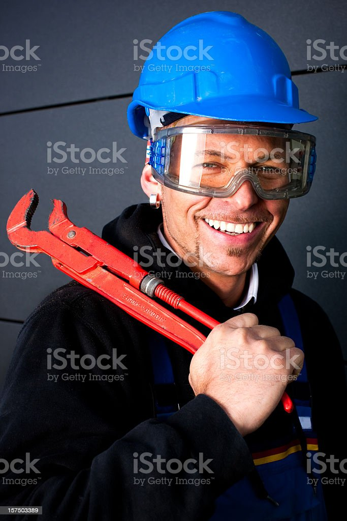 Happy Manual Worker With Blue Hardhat And Wrench royalty-free stock photo