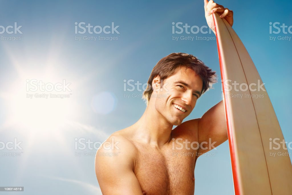 Happy masculine surfer with a surfboard against the sky royalty-free stock photo