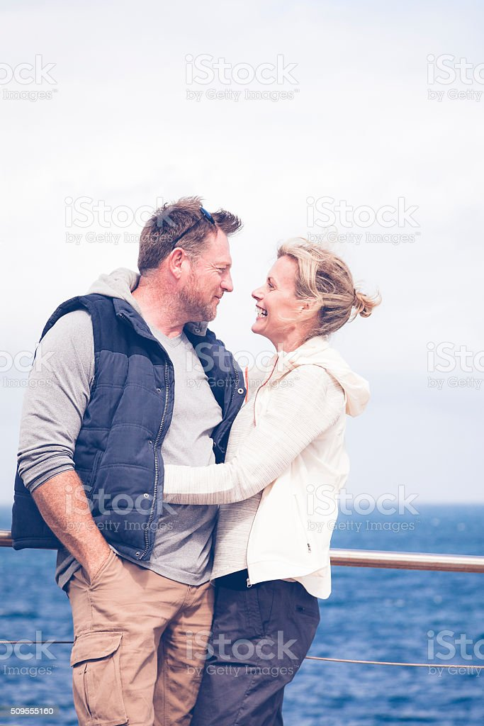 Happy mature adult couple embracing by the sea stock photo