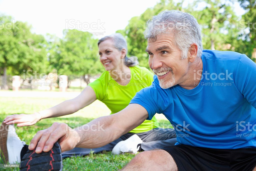 Happy Mature Adults Stretching Before Exercising stock photo