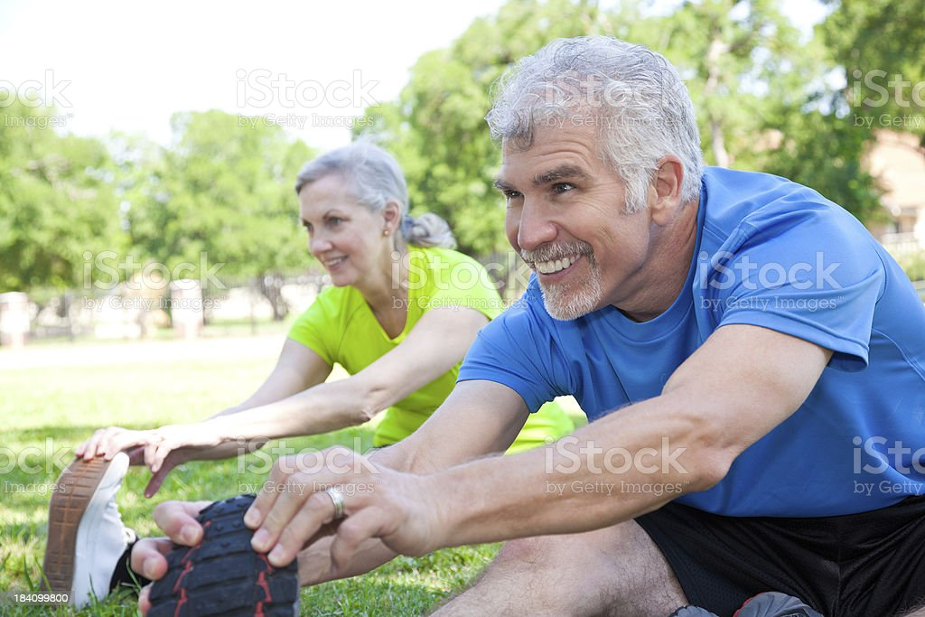 Happy Mature Adults Stretching Legs at a Park royalty-free stock photo