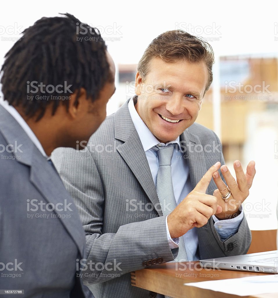 Happy mature businessman discussing with his colleague royalty-free stock photo