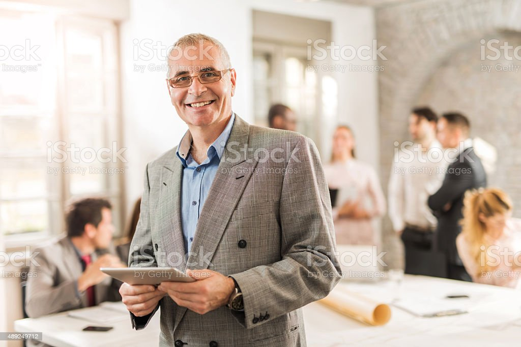 Happy mature businessman holding touchpad in the office. stock photo