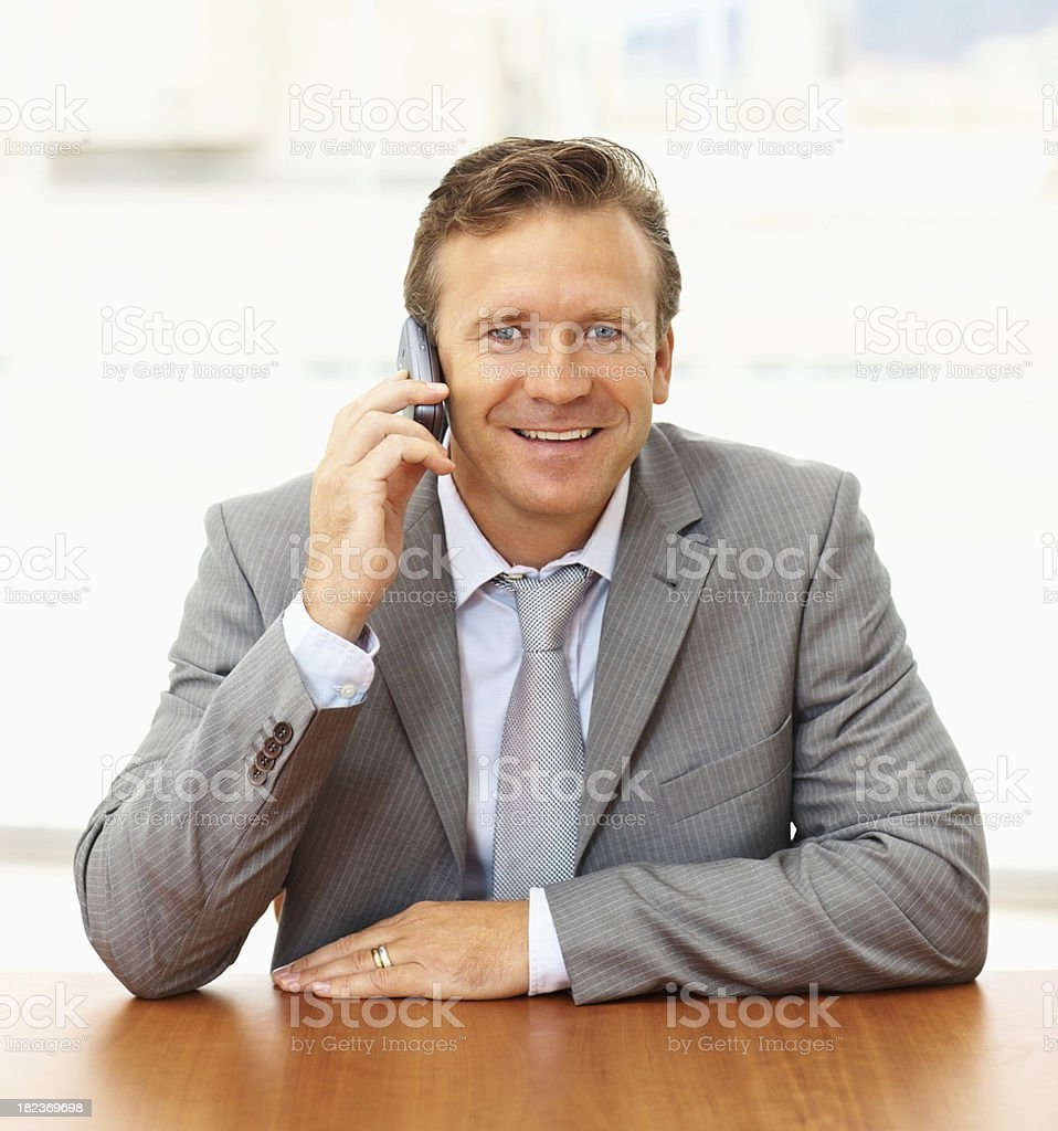 Happy mature businessman talking on a cellphone royalty-free stock photo