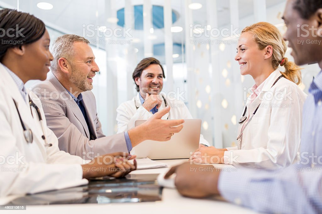 Happy mature businessman talking on a meeting with doctors. stock photo