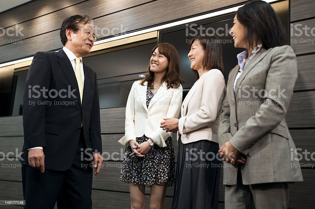 Happy mature businessman talking to his female colleagues royalty-free stock photo