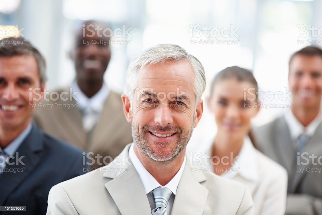 Happy mature businessman with colleagues in the background royalty-free stock photo