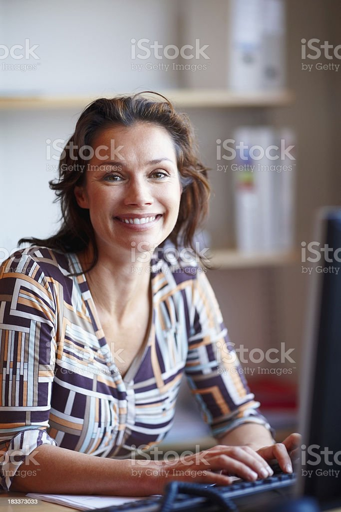 Happy mature businesswoman at office desk using computer royalty-free stock photo