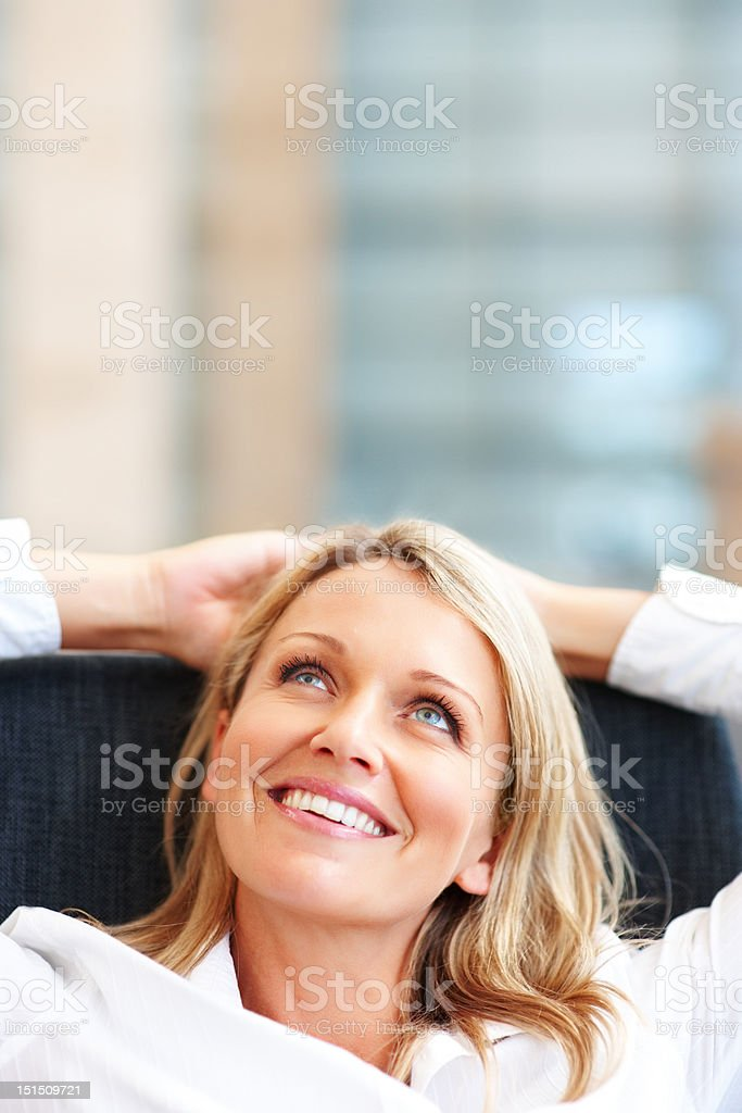 Happy mature businesswoman relaxing on chair royalty-free stock photo