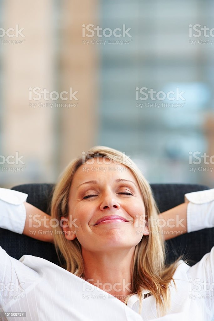 Happy mature businesswoman relaxing on chair stock photo