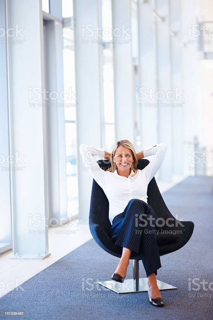 Happy mature businesswoman relaxing on office chair stock photo