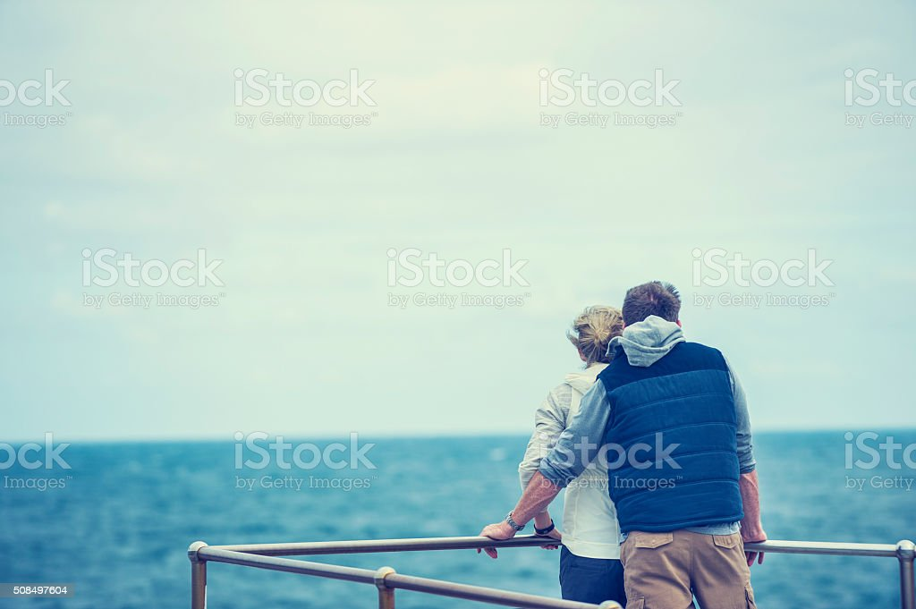 Happy mature couple at the beach. stock photo