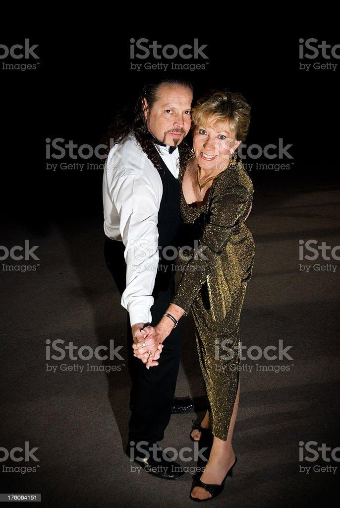 Happy mature couple dancing on a dance floor stock photo