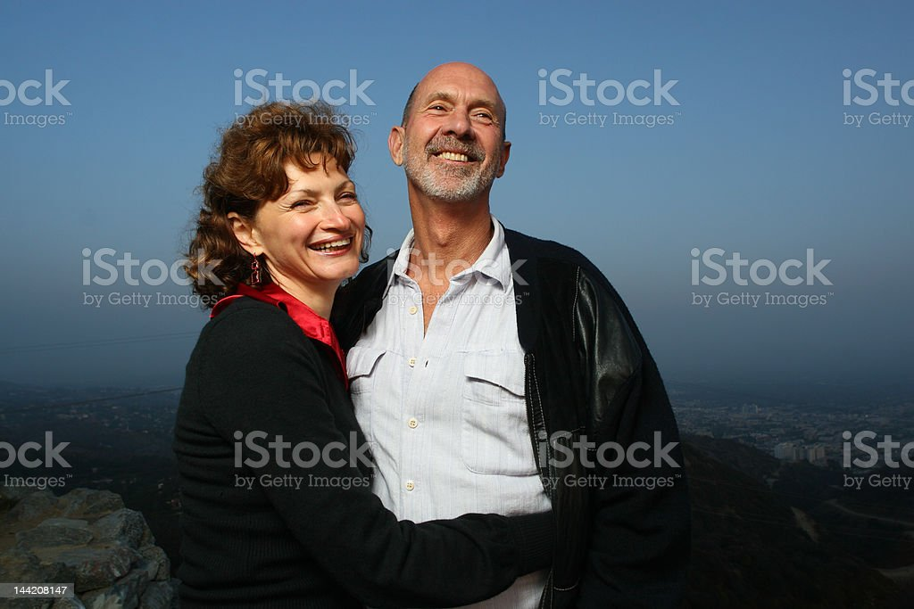 Happy mature couple embracing outdoors ontop of a city royalty-free stock photo