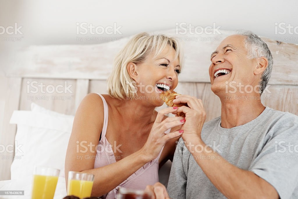 Happy mature couple enjoying their breakfast in bed royalty-free stock photo
