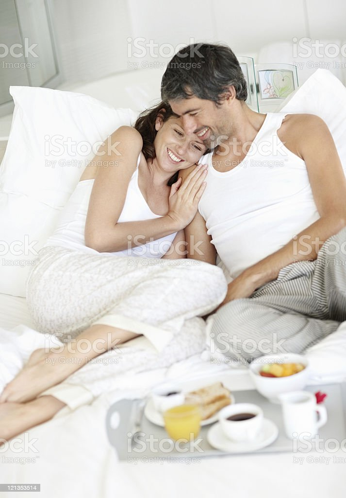 Happy mature couple having breakfast in bed royalty-free stock photo