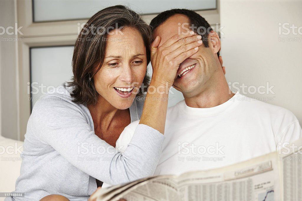 Happy mature couple having fun while reading newspaper royalty-free stock photo