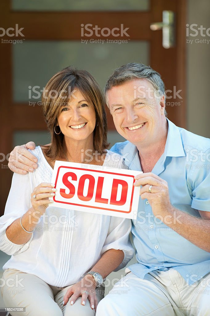 Happy mature couple holding sold sign stock photo