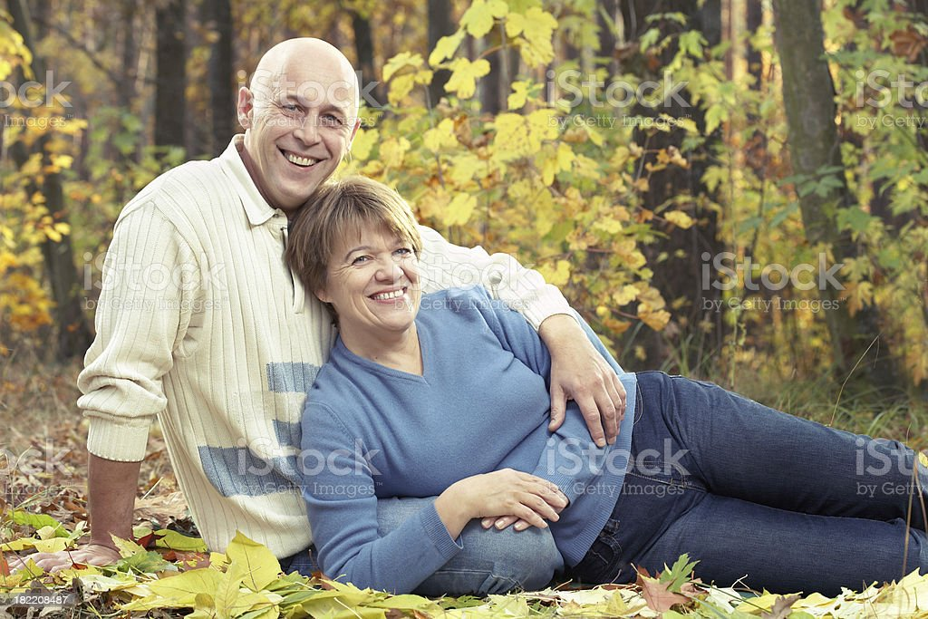 Happy mature couple in autumn forest stock photo