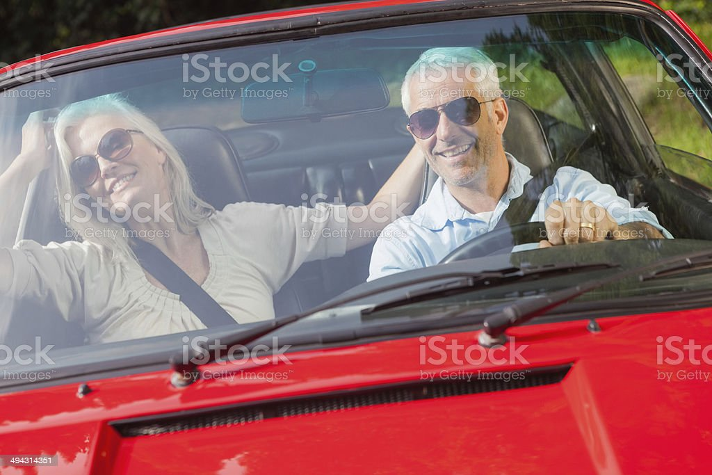 Happy mature couple in red cabriolet stock photo