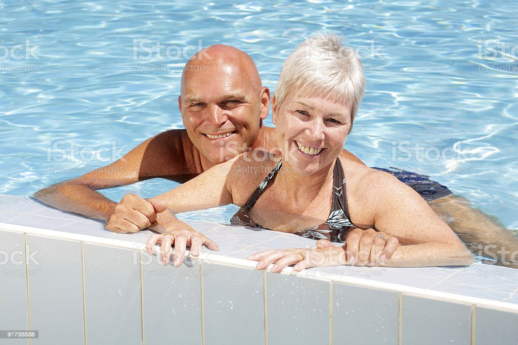 happy mature couple in swimming pool royalty-free stock photo