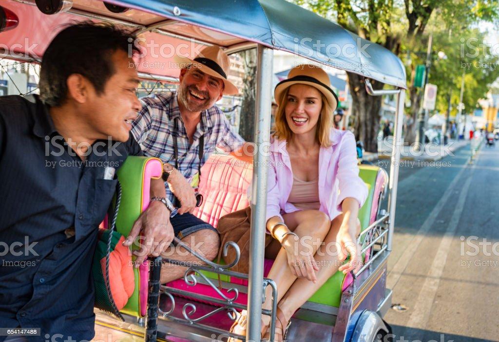 Happy Mature Couple on Vacation Using Tuktuk Transport in Thailand stock photo