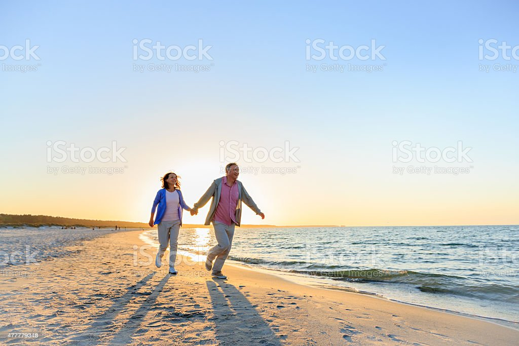 Happy mature couple outdoors on the beach stock photo