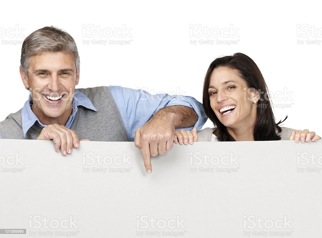Happy mature couple pointing at blank billboard stock photo