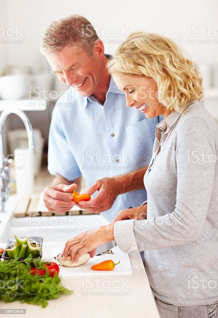 Happy mature couple preparing food together in kitchen stock photo