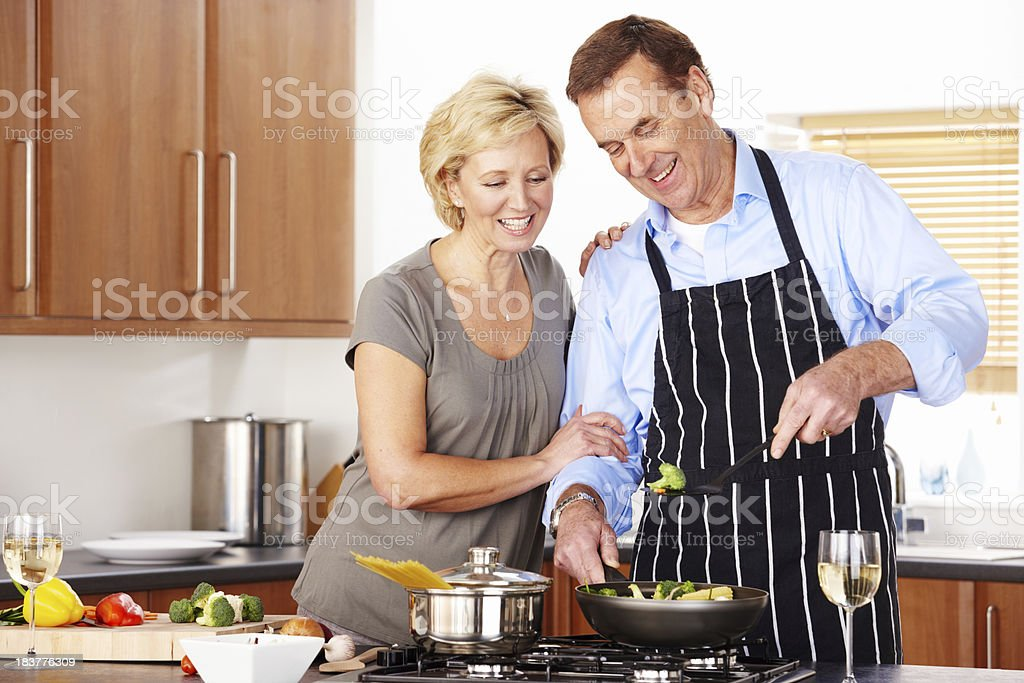 Happy mature couple preparing food together in kitchen royalty-free stock photo