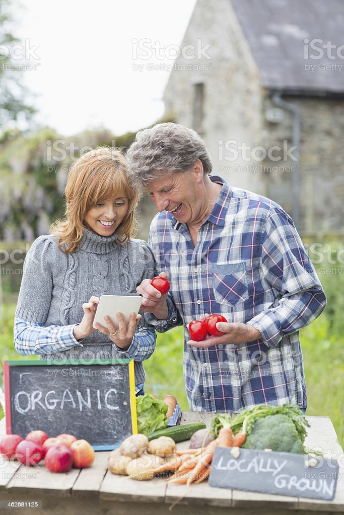 Happy mature couple preparing to sell their vegetables royalty-free stock photo